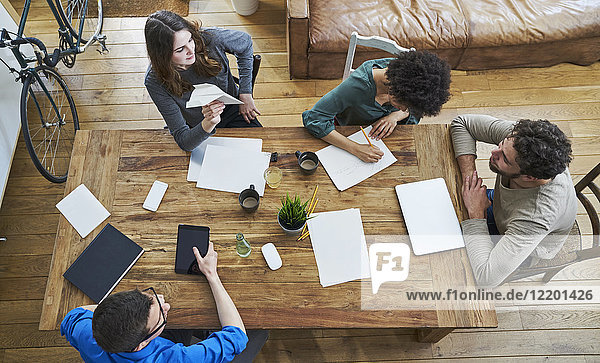 Elevated view of coworkers working together at wooden table in office