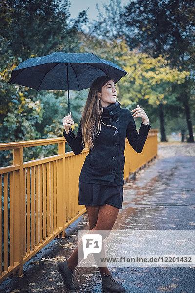 Junge Frau mit Schirm steht im Herbst auf einer Brücke