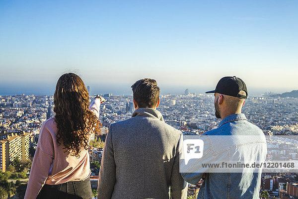 Spanien  Barcelona  drei Freunde auf einem Hügel mit Blick auf die Stadt