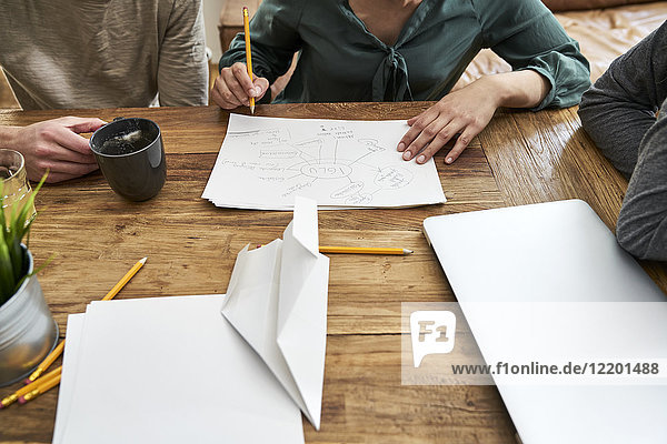 Coworkers working together and taking notes at table in office