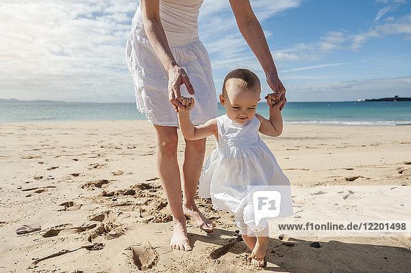 Mutter hilft der kleinen Tochter  die am Strand spazieren geht.
