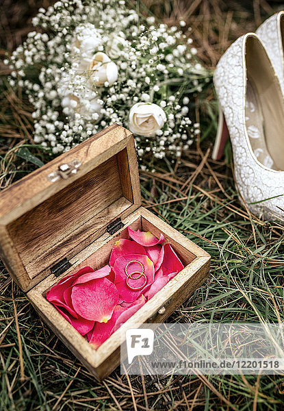 Close-up of wedding rings over red flower petals inside a casket in grass