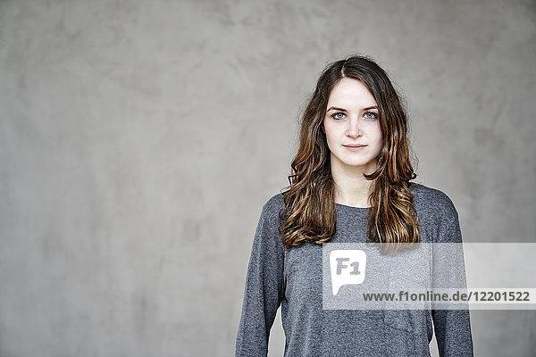 Porträt einer selbstbewussten jungen Frau vor grauer Wand