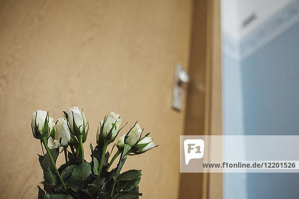 Weiße Abschiedsblumen an der Wohnungstür des verstorbenen Nachbarn