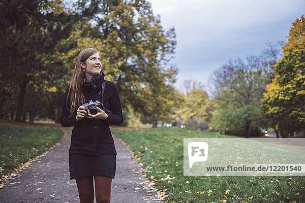Junge Frau mit Kamera beim Spaziergang im Herbstpark
