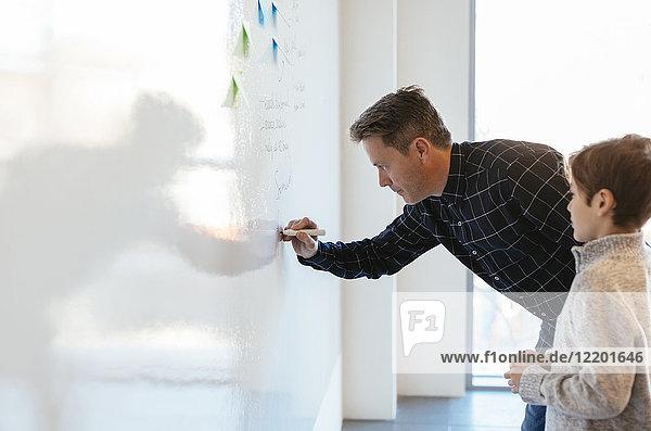 Geschäftsmann im Büro schriftlich auf Whiteboard mit Sohn beobachtet ihn