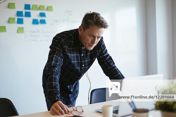 Geschäftsmann am Schreibtisch im Büro mit Blick auf Laptop