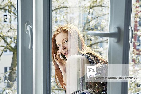 Porträt einer rothaarigen Frau am Telefon  die sich im Frühjahr aus dem Fenster lehnt.