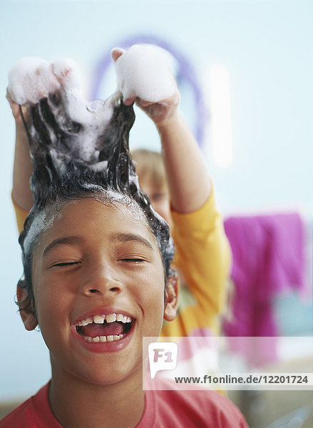 Portrait of laughing little boy with foam in his hair