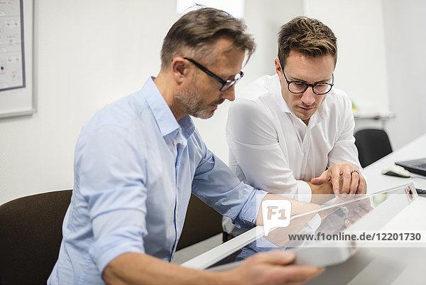 Zwei Geschäftsleute untersuchen Solarpanel auf dem Schreibtisch im Büro