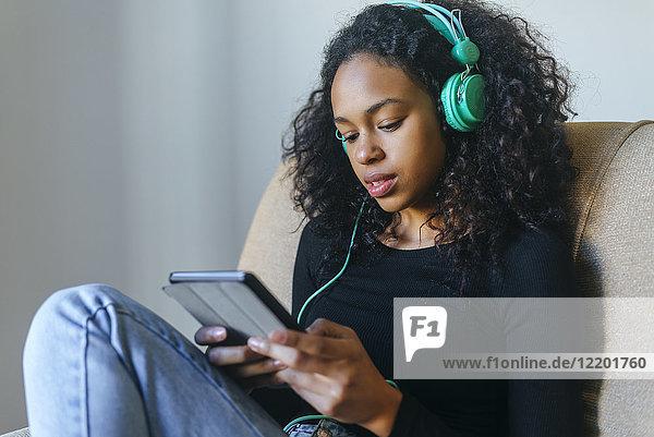 Portrait einer jungen Frau  die im Sessel sitzt und Musik mit Kopfhörer und Tablett hört.