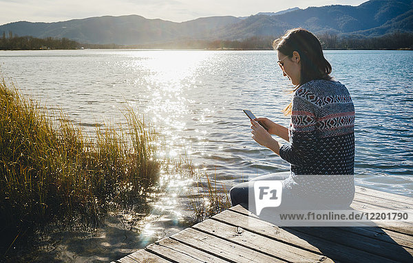Woman sitting on a wooden platform at a lake at sunset  using smartphone