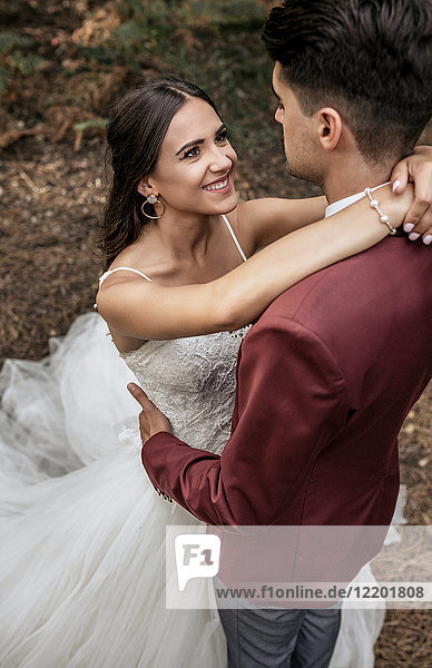 Portrait of beautiful bride embracing and looking to man outdoors