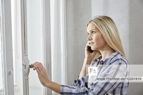Blonde Frau am Telefon  die aus dem Fenster schaut.
