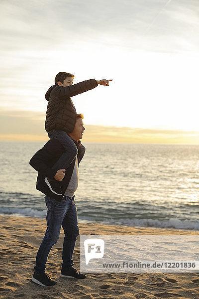 Vater trägt Sohn Huckepack am Strand bei Sonnenuntergang mit dem Finger