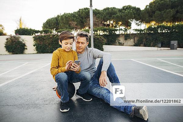 Vater und Sohn sitzen auf dem Basketballfeld mit dem Handy