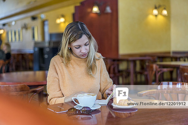 Young woman in a cafe with notebook  pastry and coffee