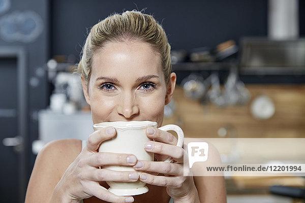 Porträt einer lächelnden blonden Frau in der Küche mit Kaffeetasse