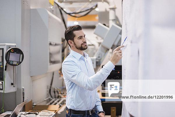Geschäftsmann in der Fabrik mit Blick auf den Plan