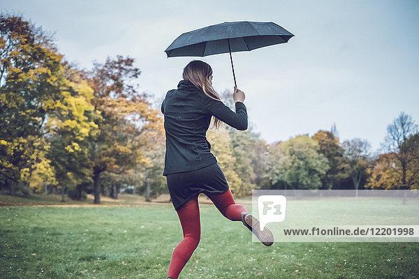 Rückansicht der jungen Frau mit Regenschirm im herbstlichen Park