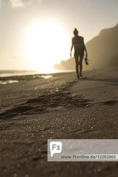 Indonesien  Bali  Frau am Strand bei Sonnenuntergang