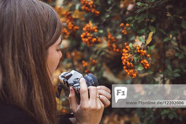 Junge Frau fotografiert mit alter Kamera in herbstlicher Natur