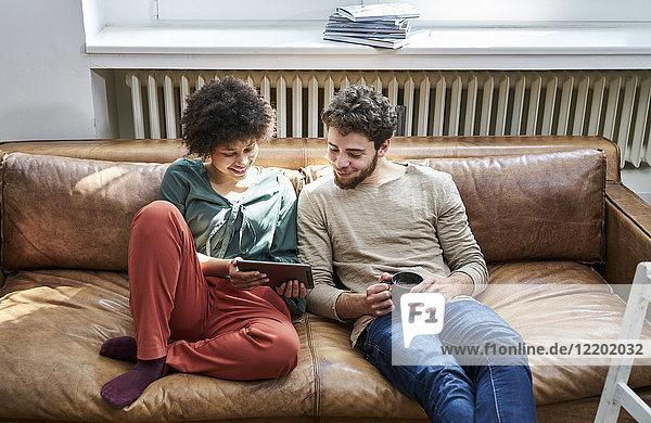 Junger Mann und junge Frau sitzend auf der Couch mit Tasse Kaffee und Tablette