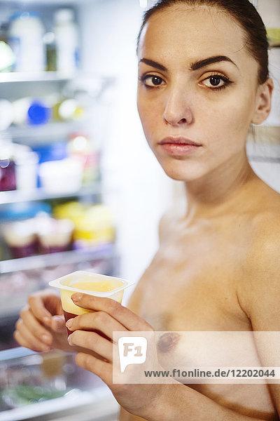 Porträt einer nackten jungen Frau mit süßem Dessert am Kühlschrank