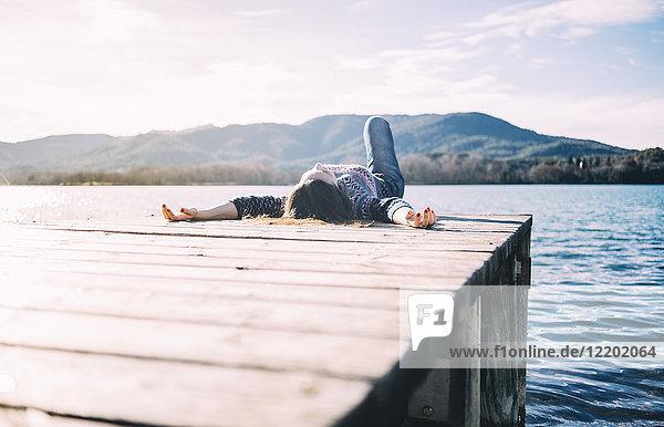 Frau ruht auf einem Holzsteg am See