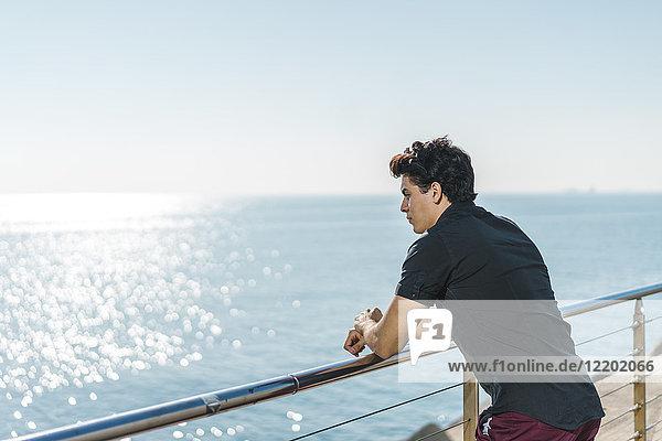 Junger Mann an der Küste mit Blick auf das Meer