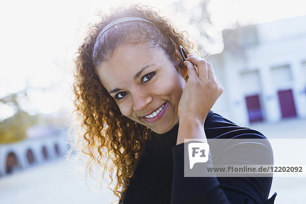 Portrait of smiling young woman outdoors putting on earphone