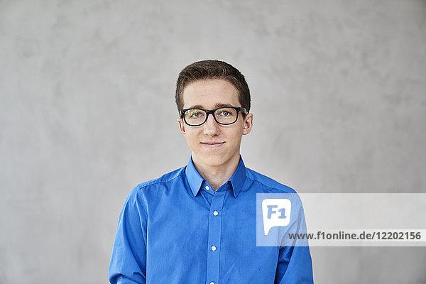 Porträt eines selbstbewussten jungen Mannes mit blauem Hemd