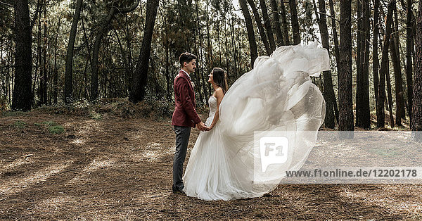 Bride with windswept wedding dress and groom standing in forest holding hands
