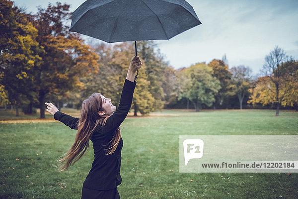 Fröhliche junge Frau tanzt mit Regenschirm im herbstlichen Park