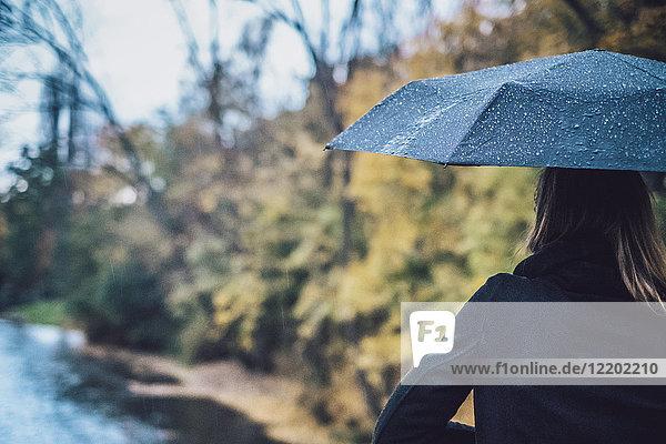 Rückansicht der jungen Frau mit nassem Regenschirm im Herbst