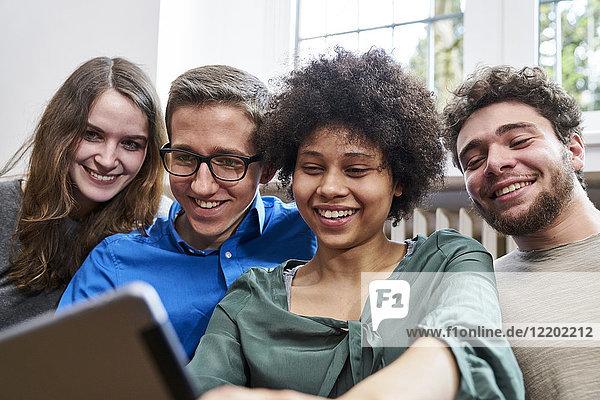 Lächelnde junge Leute schauen auf die Tablette