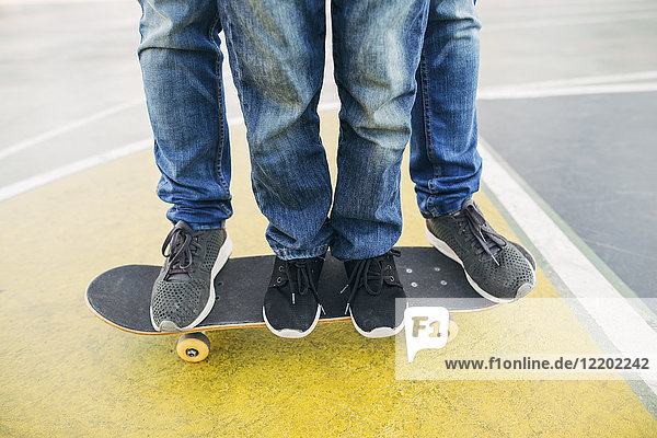 Beine von Erwachsenen und Kindern auf dem Skateboard