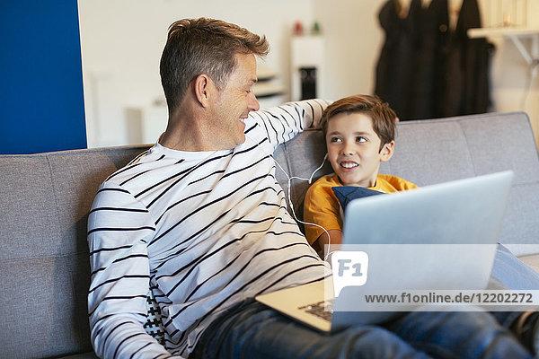 Lächelnder Vater und Sohn mit Ohrstöpseln und Laptop auf der Couch zu Hause