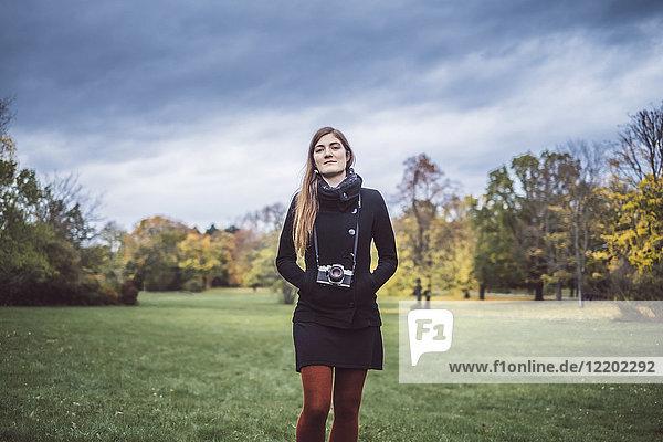 Portrait einer jungen Frau mit Kamera auf einer Wiese im herbstlichen Park