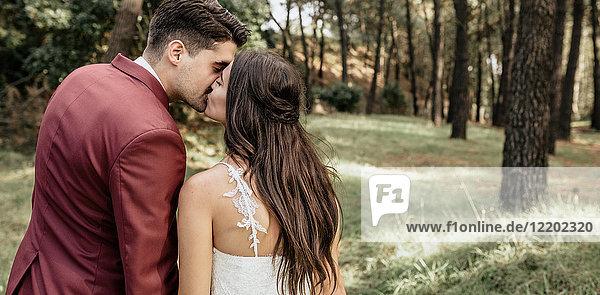 Rückansicht von Braut und Bräutigam beim Küssen im Wald