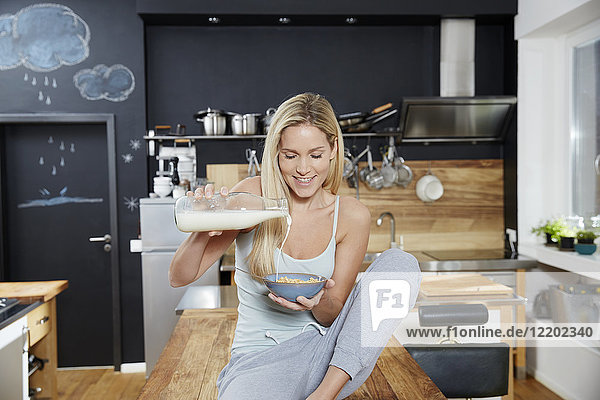 Blonde Frau sitzt auf dem Küchentisch und gießt Milch auf Getreide.