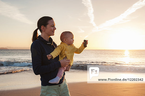 Mother holding little daughter on the beach at sunset