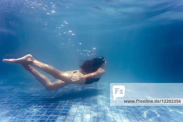 Junge Frau unter Wasser im Schwimmbad