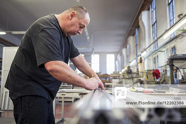 Mann in der Fabrik bei der Bearbeitung von Metallteilen