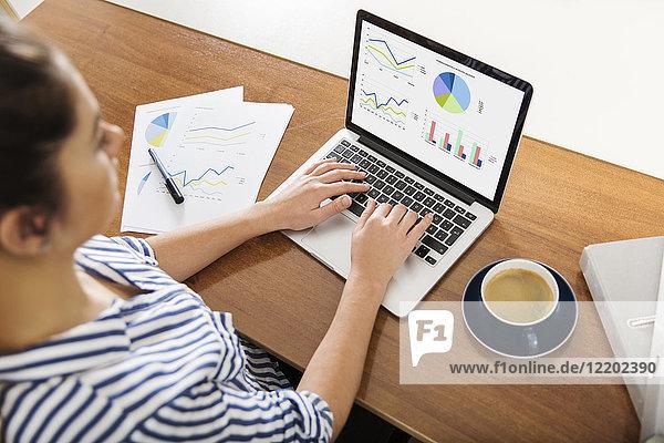 Junge Frau  die zu Hause an den Charts ihres Laptops arbeitet