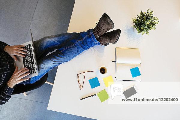 Geschäftsmann mit Laptop mit Füßen auf dem Schreibtisch im Büro