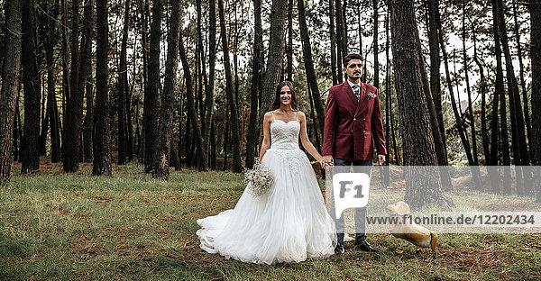 Happy bride and groom standing in forest with funny dog-shaped balloon