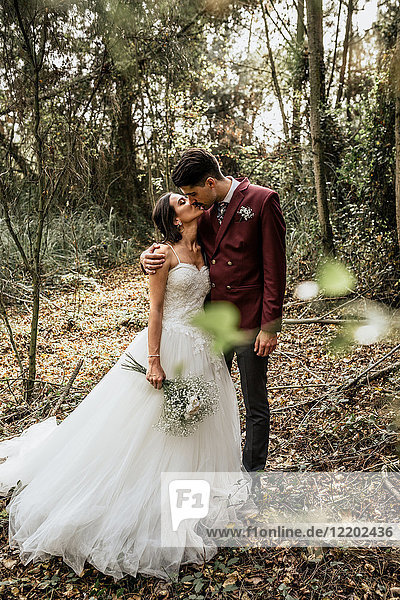 Bride and groom standing in forest kissing