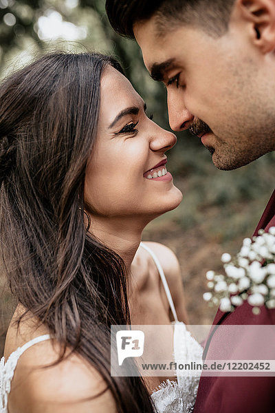 Portrait of happy and smiling bride looking at man with moustache outdoors