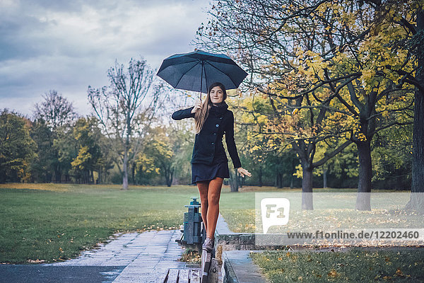 Junge Frau mit Regenschirm auf der Rückenlehne der Bank im Herbstpark